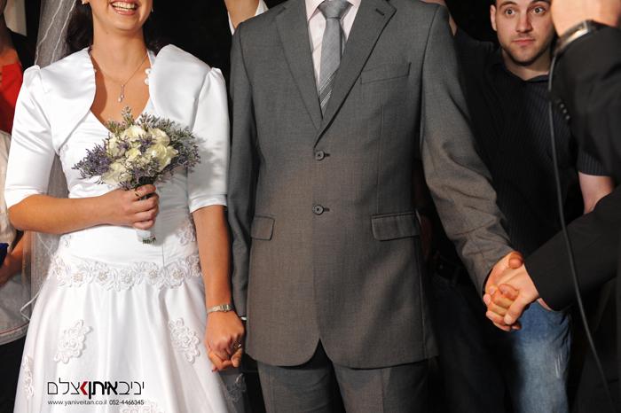 חתן וכלה אוחזים ידיים עם הרב מתוך צילום חתונה בארץ קדם