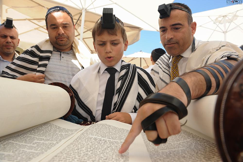 חתן הבר מצווה בעליה לתורה בכותל המערבי בירושלים
