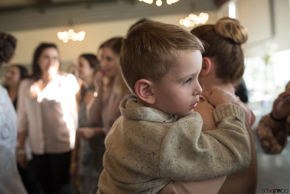 הילד הרגוע על כתפי אמו בחתונה