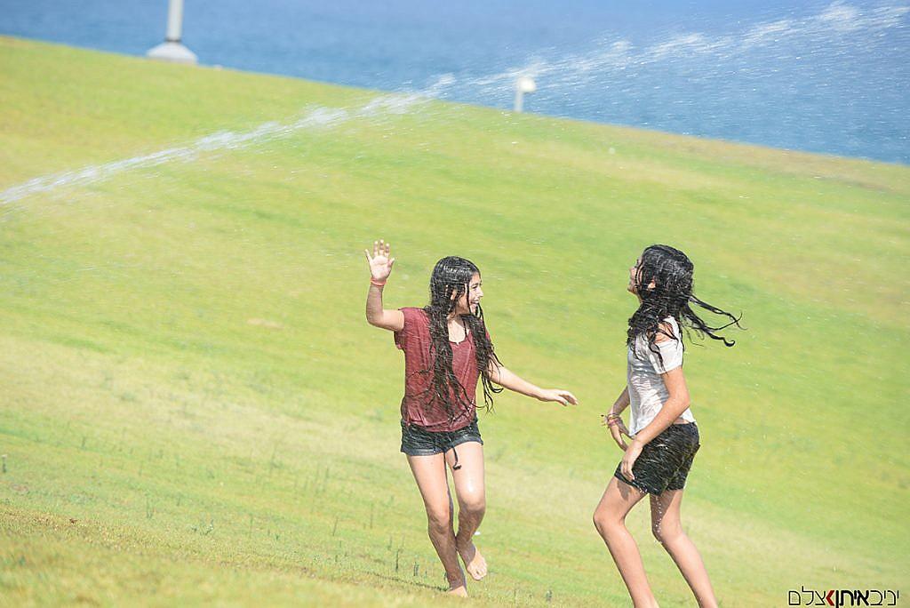 שתי אחיות מקסימות משחקות בממטרות בנמל יפו