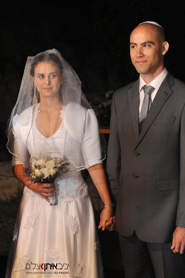 צילום חתן וכלה בחופה אוחזים ידיים בדרכם החדשה. מזל טוב