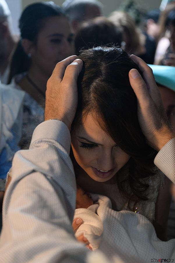 האמא המאושרת חובקת את הרך הנולד בטקס המילה ומקבלת ברכה מהסנדק - צלם ברית מומלץ
