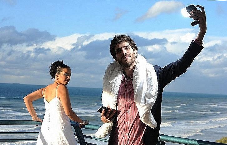 חתן וכלה מצטלמים ביום הסערה על שפת הים בנתניה