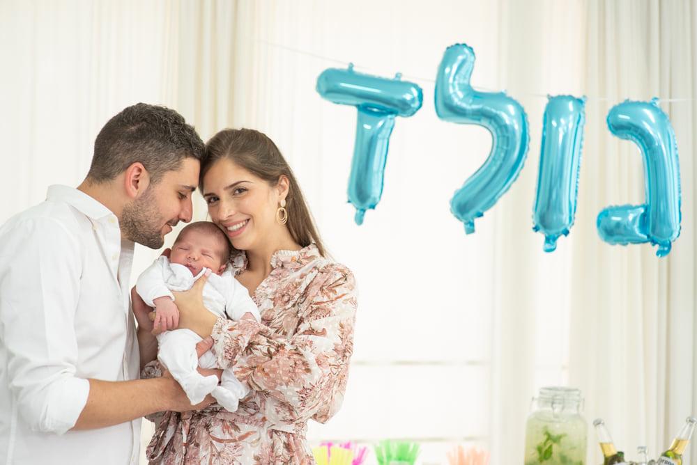 ההורים השמחים בתמונה משפחתית עם התינוק הנולד