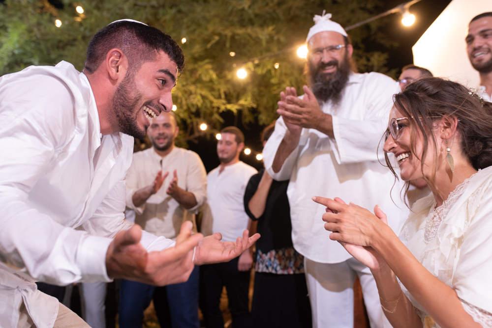 החתן מרקד בשמחה ובהתרגשות לפני הכלה הדומעת