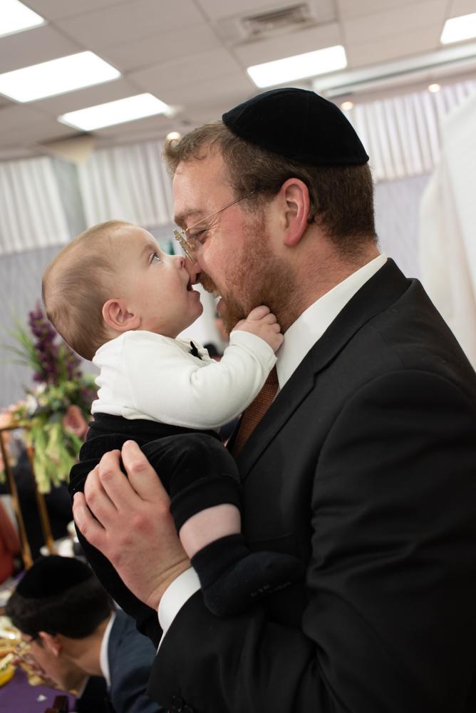 נשיקת האב השמח תינוק בטקס הברת