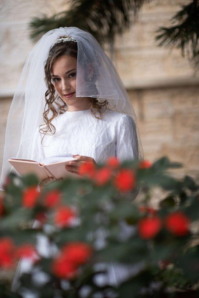 צילום הכלה בתפילה מבעד לורדים האדומים