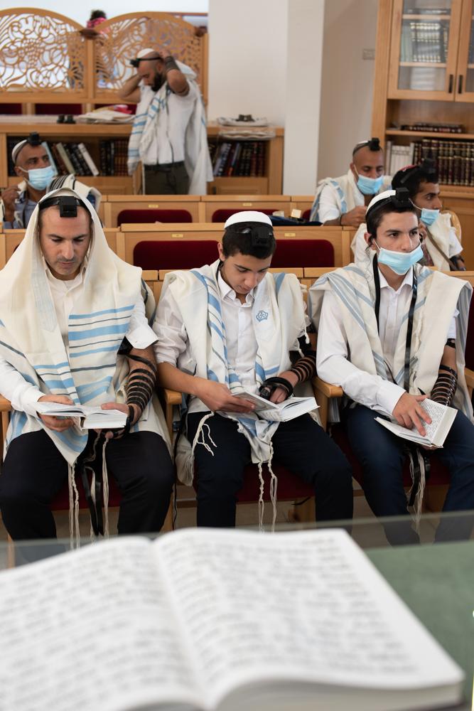 חתן הבר מצווה בתפילת שחרית עם אביו ואחיו