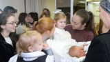 האחות בידיים האוהבות של הדודה מסתכלת על התינוק
