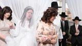 הכלה מלווה באימהות מקיפה את החתן בחופה