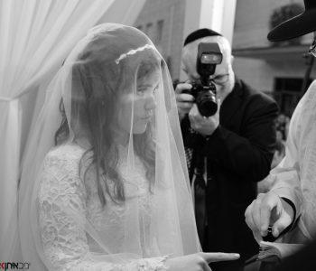 החתן עונד את טבעת הנישואין לכלה החסידית